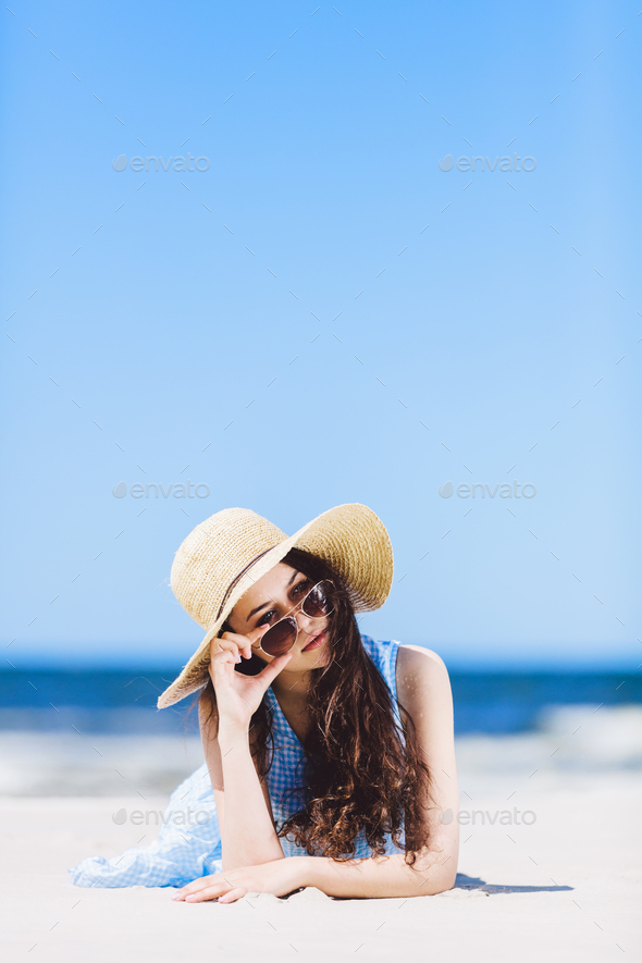 Young pretty woman laying on the beach, holding her sunglasses. - Stock Photo - Images