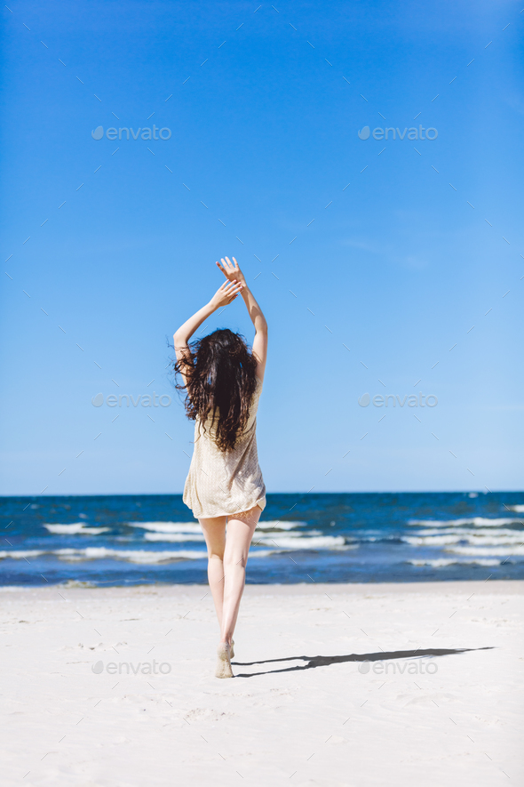 Young girl walking on the beach, holding her hands up. - Stock Photo - Images