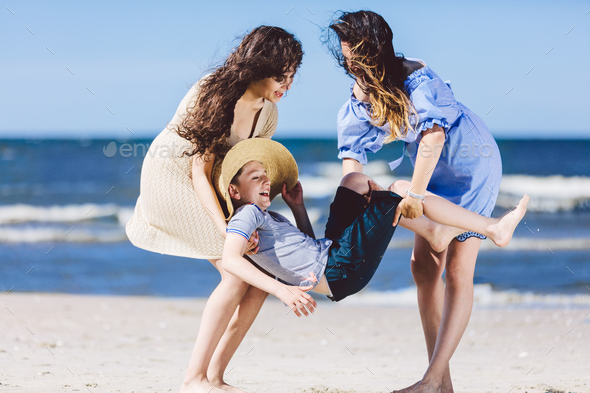 Two women carrying a boy in a straw hat on the beach. - Stock Photo - Images