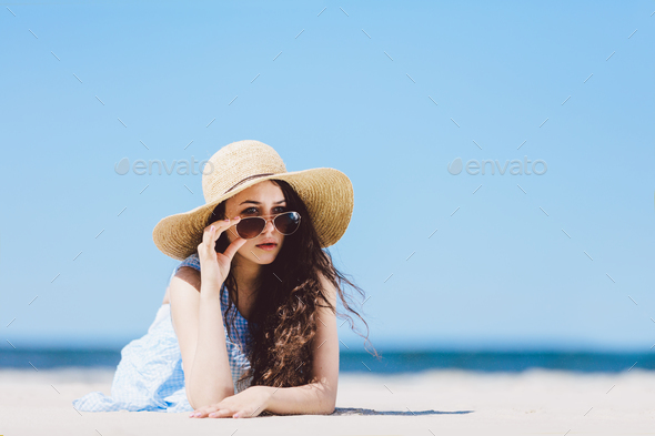Pretty girl in straw hat laying on the sandy beach - Stock Photo - Images