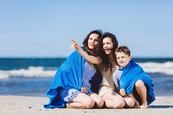 Family sitting on a beach, older sister pointing her finger - Stock Photo - Images