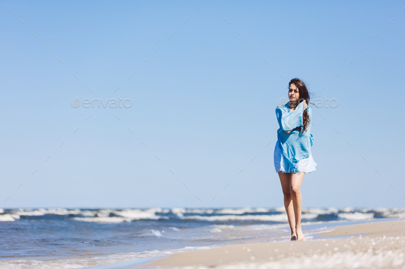Young girl walking by the sea, wrapped in a blue scarf. - Stock Photo - Images