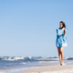 Young girl walking by the sea, wrapped in a blue scarf. - PhotoDune Item for Sale