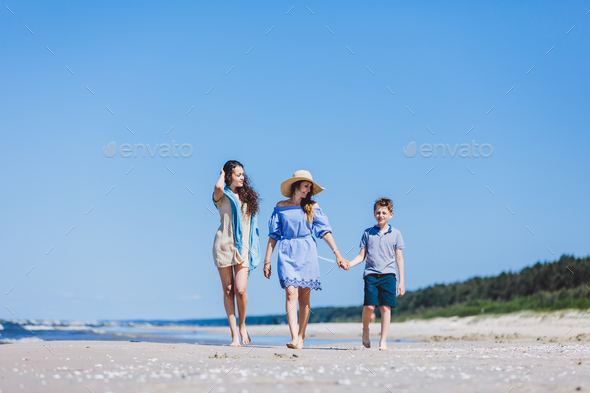 Mother and her two children walking on the beach - Stock Photo - Images
