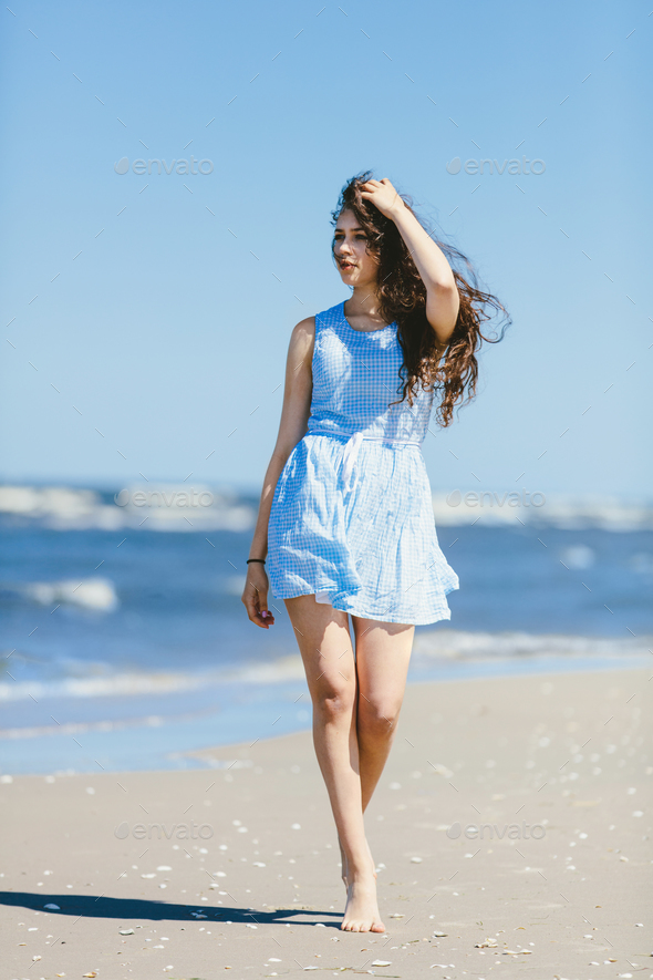 Young girl casually walking on a coast - Stock Photo - Images