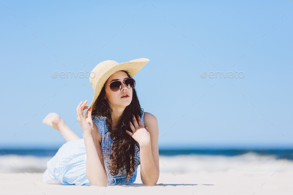 Young girl laying on the beach in a hat and sunglasses - Stock Photo - Images