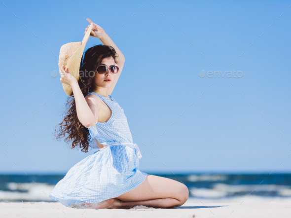 Pretty girl sitting on a sandy beach by the blue sea. - Stock Photo - Images