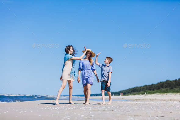 Mother with children walking by the sea - Stock Photo - Images