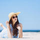Young girl laying on the beach in a hat and sunglasses - PhotoDune Item for Sale