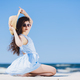 Pretty girl sitting on a sandy beach by the blue sea. - PhotoDune Item for Sale