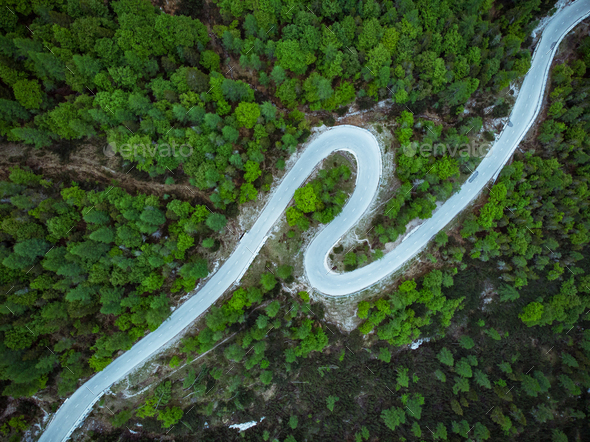 Curved road trough forest , birds eye drone aerial view - Stock Photo - Images