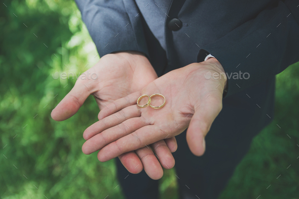 Two golden wedding rings on groom's palms. Wedding rings on the - Stock Photo - Images