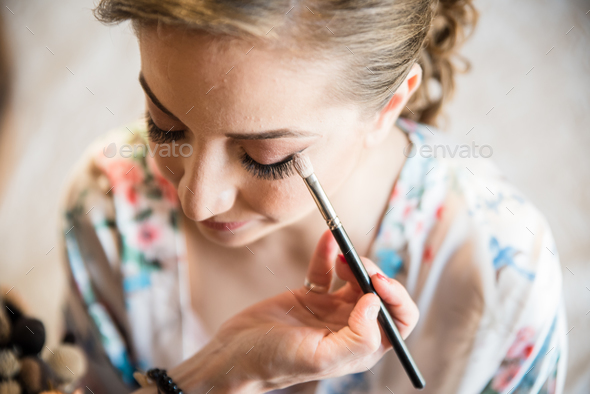 Makeup artist preparing bride before the wedding. - Stock Photo - Images