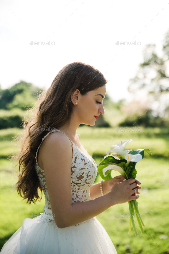 Young beautiful bride holding bouquet. Soft sunset light - Stock Photo - Images