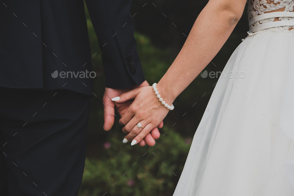 Young married couple holding hands - Stock Photo - Images