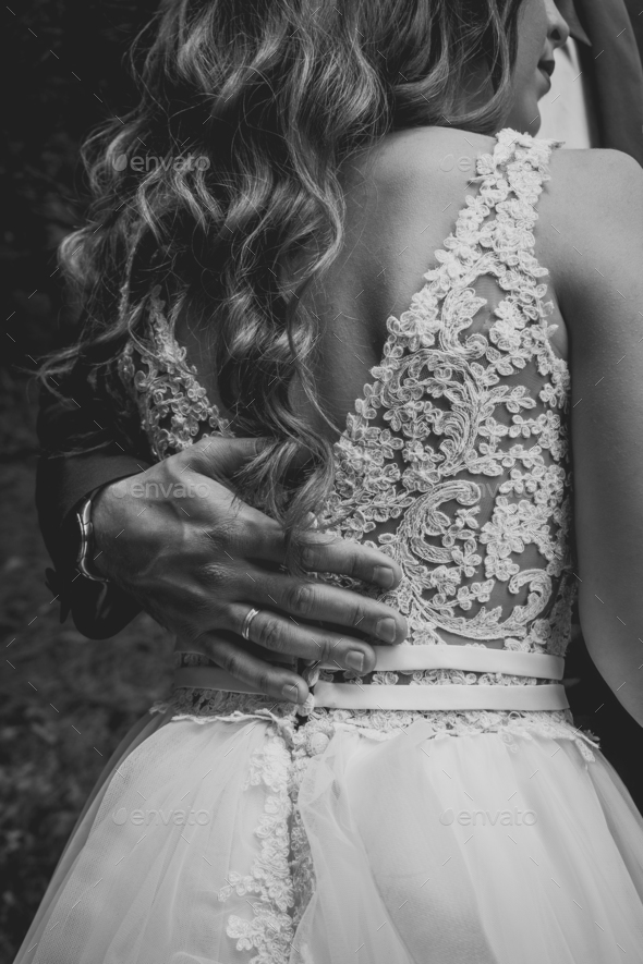 The bride and groom hugging. Ring on grooms hand. - Stock Photo - Images