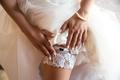 Bride putting a wedding garter on her leg - PhotoDune Item for Sale