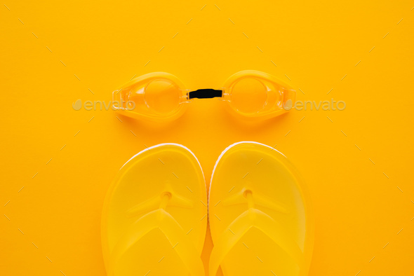 Swimming goggles and flip flops on yellow background - Stock Photo - Images
