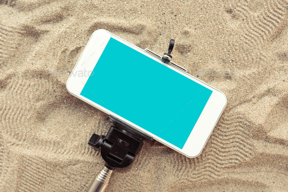 Smartphone on selfie stick in beach sand - Stock Photo - Images