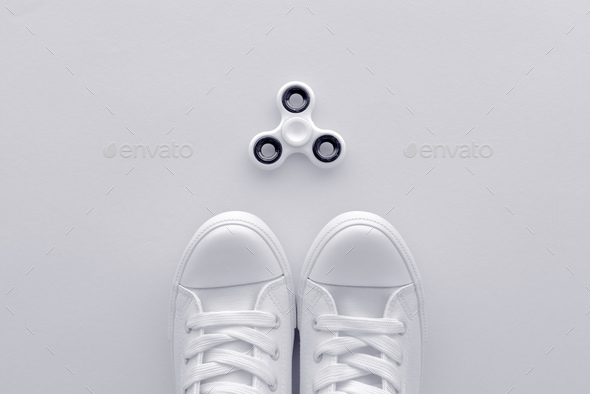 Sneakers and fidget spinner flay lay top view - Stock Photo - Images