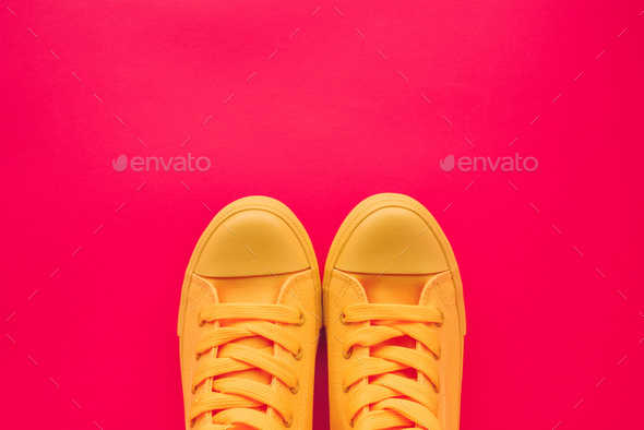 Yellow canvas shoes sneakers on neon pink background - Stock Photo - Images