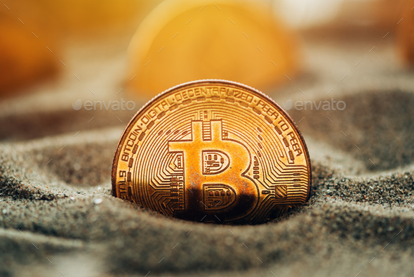 Bitcoins in sand - Stock Photo - Images