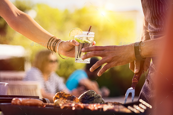 Woman sharing drink at bbq - Stock Photo - Images