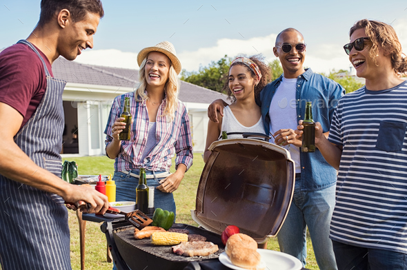 Friends enjoying party with bbq - Stock Photo - Images