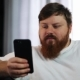 Serious Fat Man Works with His Smartphone Sitting on the Couch - VideoHive Item for Sale