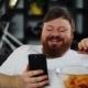 Fat Man Smiles While He Reads Something in His Smartphone and Eats Potato Chips - VideoHive Item for Sale