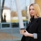 Pretty Young Blonde Woman Stands with a Cup of Coffee Before a Mirror Wall Outside - VideoHive Item for Sale