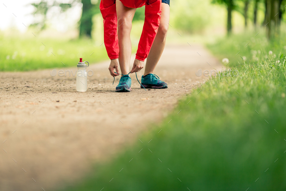 Woman runner tying sport shoes in summer park - Stock Photo - Images
