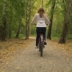 Young Woman Is Riding Bicycle in the Park Autumn and Falling Yellow Leaves - VideoHive Item for Sale