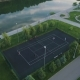 Flying Over Players Playing Tennis on a Court in Green City Park Aerial View - VideoHive Item for Sale