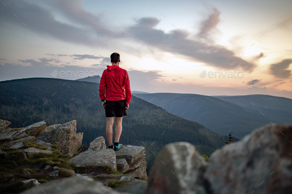 Man celebrating sunset looking at view in mountains - Stock Photo - Images