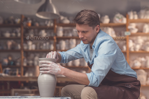 Young man with a potter's wheel - Stock Photo - Images