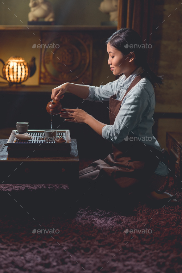 Young tea master pouring tea indoors - Stock Photo - Images