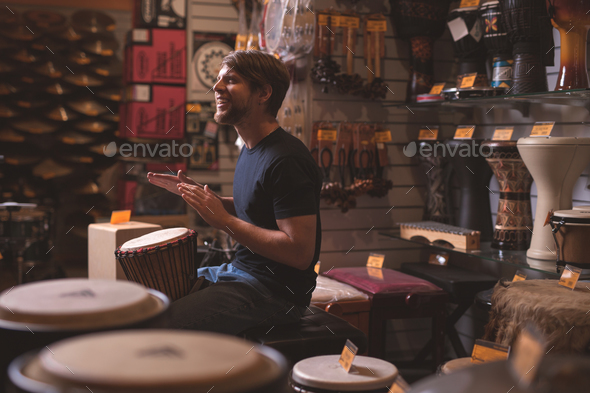 Young musician playing drums in the store - Stock Photo - Images