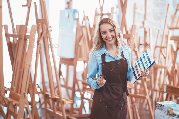 Happy young woman with easels - Stock Photo - Images