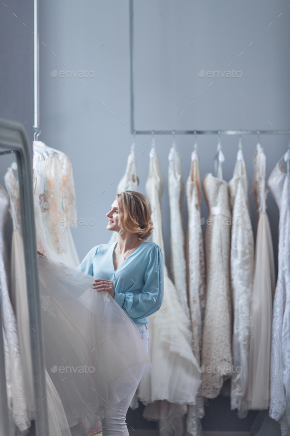 Young customer chooses a wedding dress in the store - Stock Photo - Images