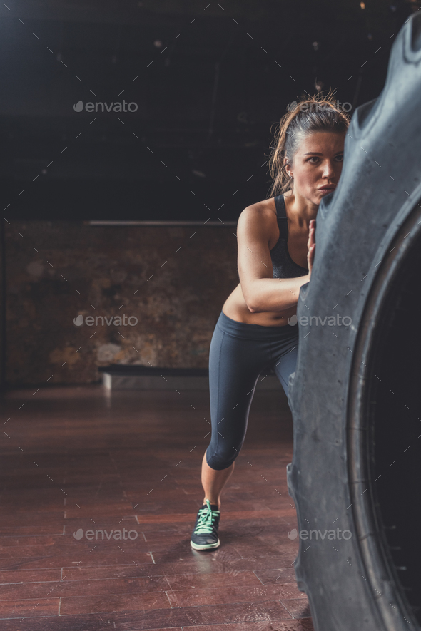 Young woman with a crossfit wheel - Stock Photo - Images