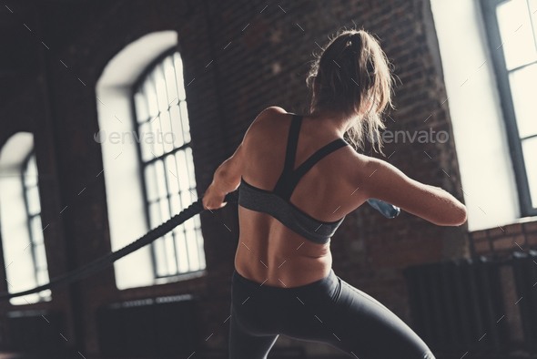 Sporty girl pulling a rope - Stock Photo - Images