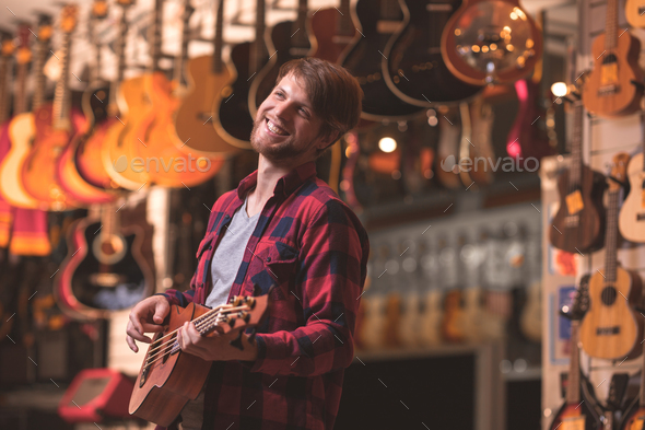 Smiling musician playing the guitar - Stock Photo - Images