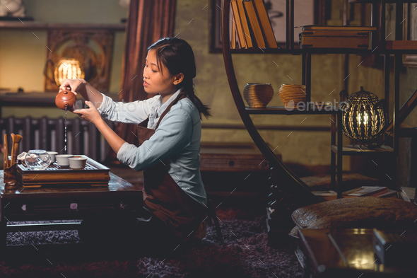 Young woman pouring tea indoors - Stock Photo - Images