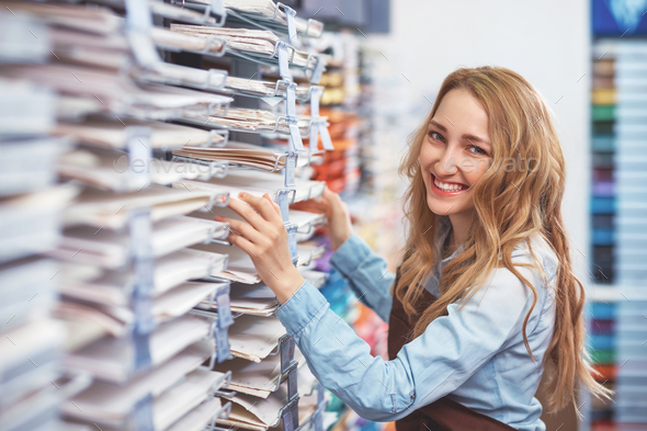 Smiling young girl in a shop - Stock Photo - Images