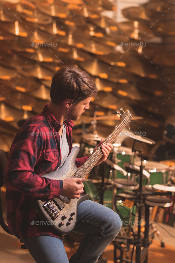 Young musician playing the guitar indoors - Stock Photo - Images