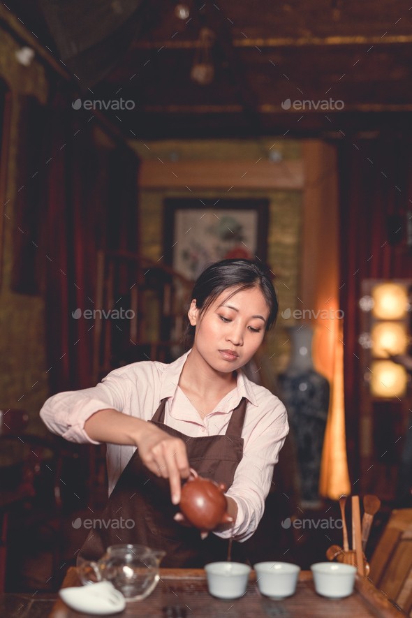 Young asian girl pouring tea - Stock Photo - Images