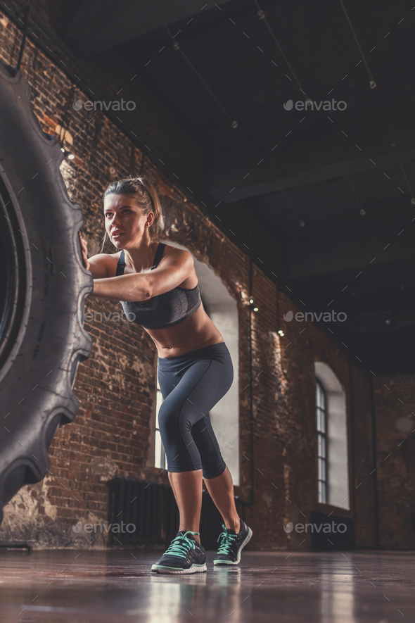 Athletic woman with a crossfit wheel - Stock Photo - Images