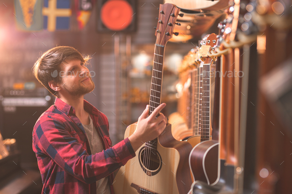 A young man chooses a guitar - Stock Photo - Images