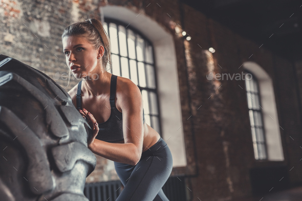 Young athletic woman with a wheel in the loft - Stock Photo - Images
